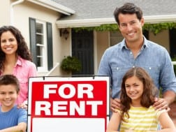 family in front of house with for rent sign